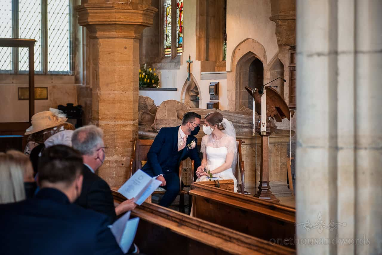 Bride and groom affectionate moment kissing through COVID facemasks in church wedding ceremony