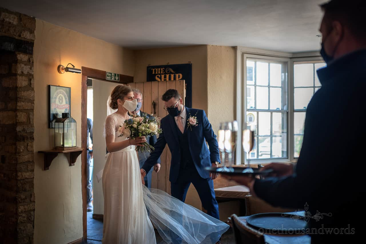 Bride and groom arrive at English pub venue to be greeted with champagne