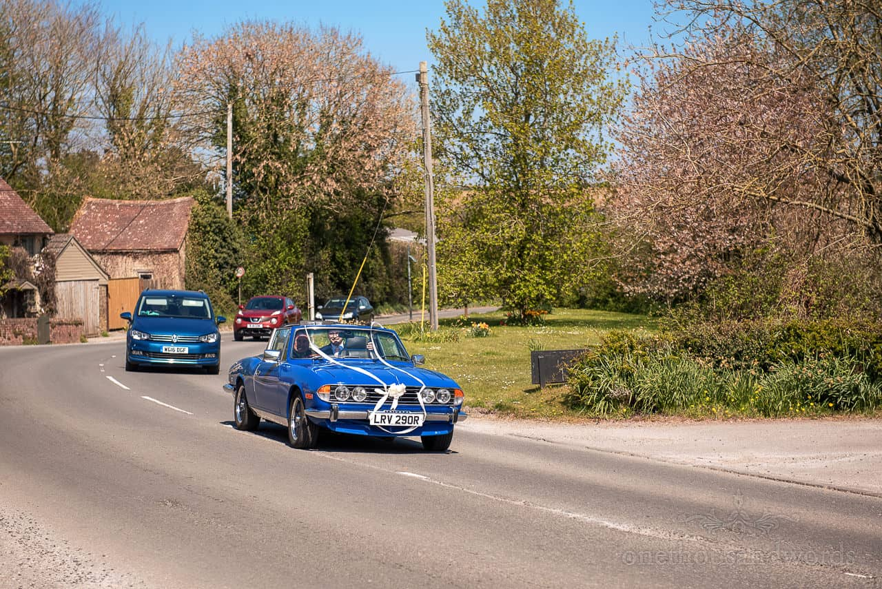 Blue Triumph Stag open top wedding car with white ribbons driving through UK countryside
