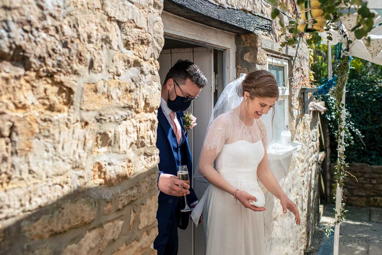 Smiling bride and groom in COVID mask exit stone doorway into wedding drinks reception