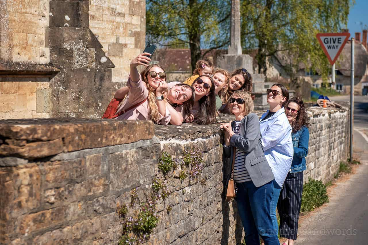 Bride and groom's group of friends take selfie in bright sun outside stone church