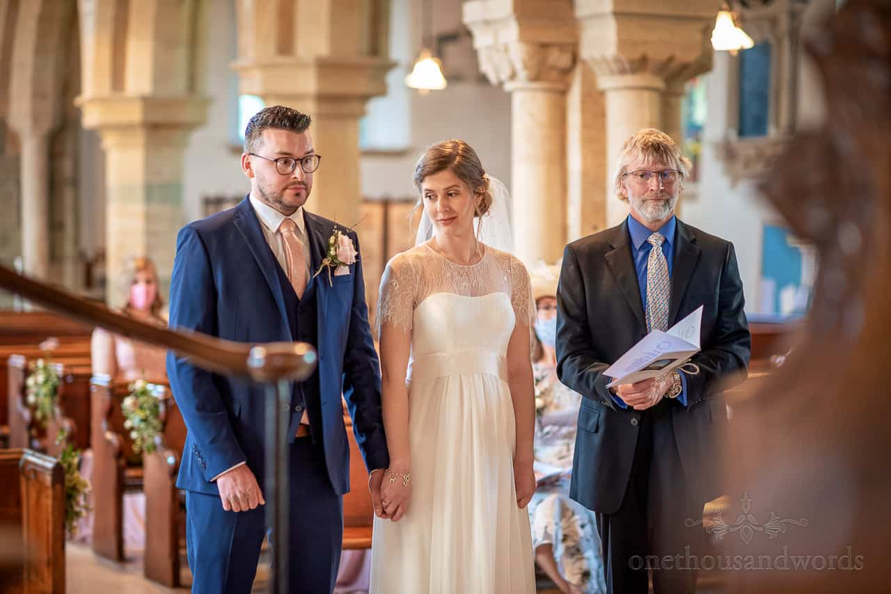 Bride and groom pull funny faces whilst holding hands during any objections part of church wedding ceremony