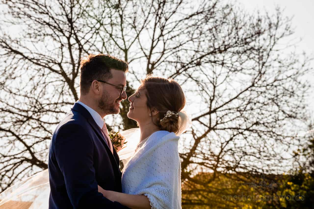 Bride and groom kissing wedding couple photograph backlit with low sun against tree