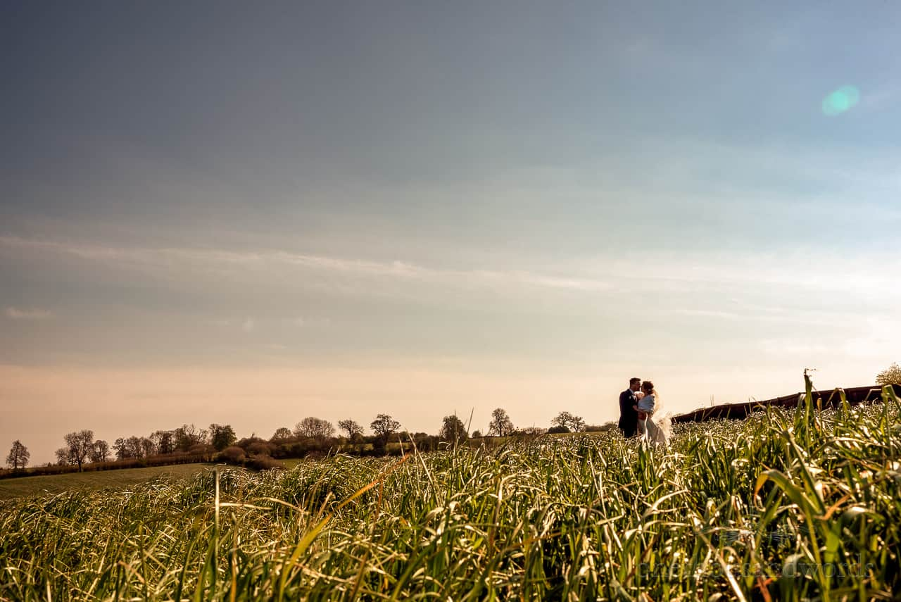 Bride and groom kissing in green Dorset countryside field