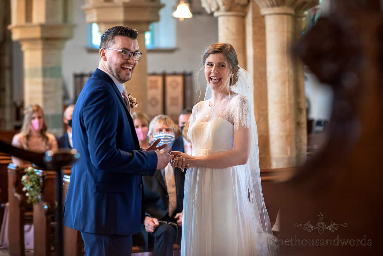 Documentary intimate wedding photography of bride and groom laughing during ring exchange in church