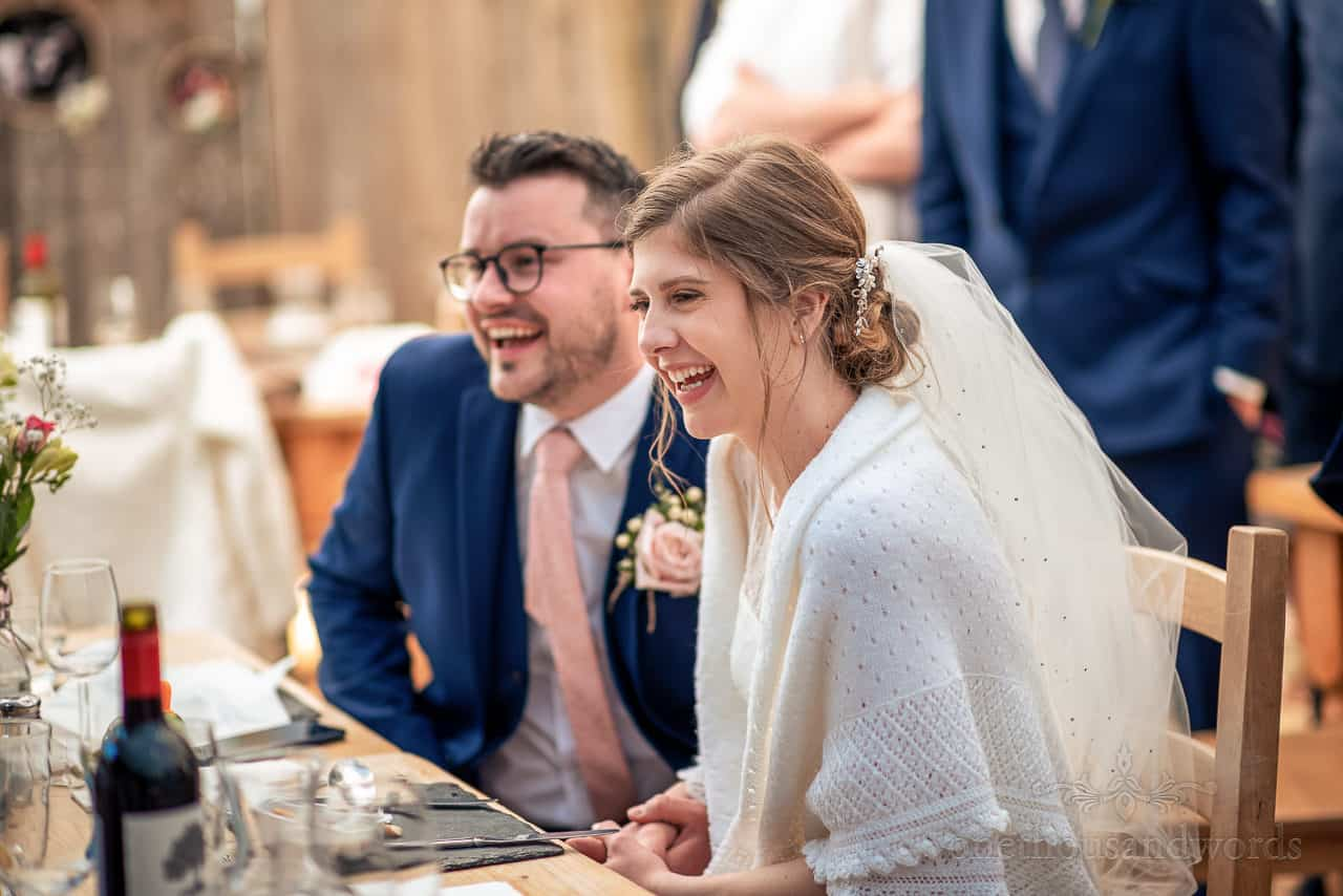 Bride and groom laughing and holding hands during wedding breakfast portrait photograph
