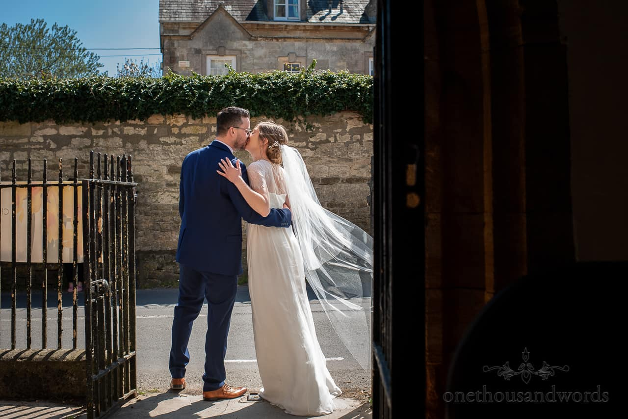 Newlyweds bride and groom share passionate kiss outside church doorway