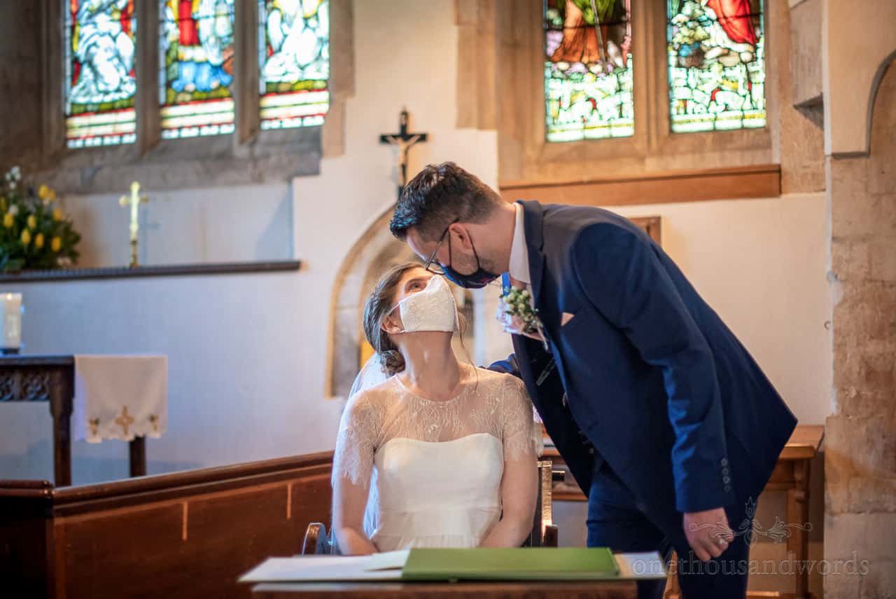 Bride and groom try kissing through wedding COVID masks whilst signing the register