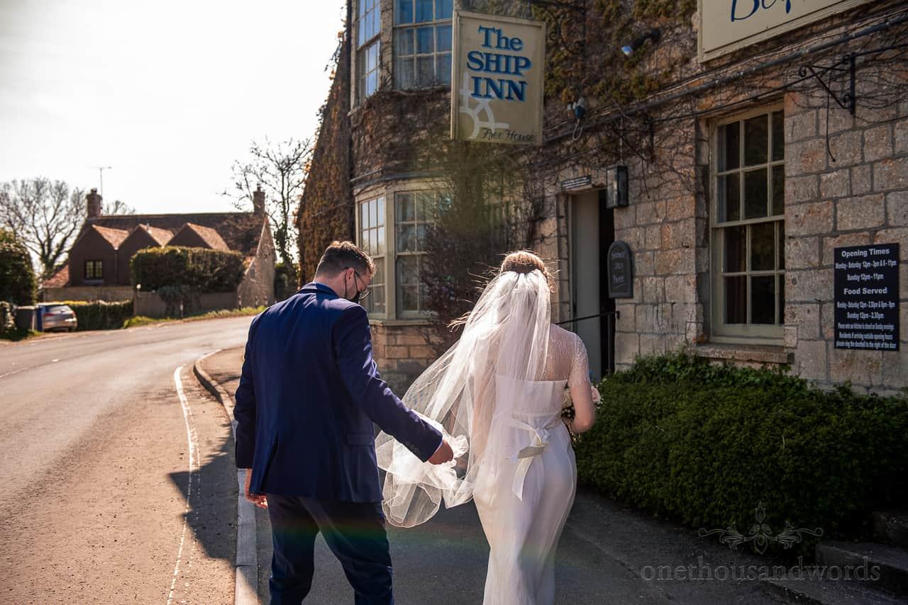 Bride and groom walk across road to The Ship Inn pub wedding reception venue