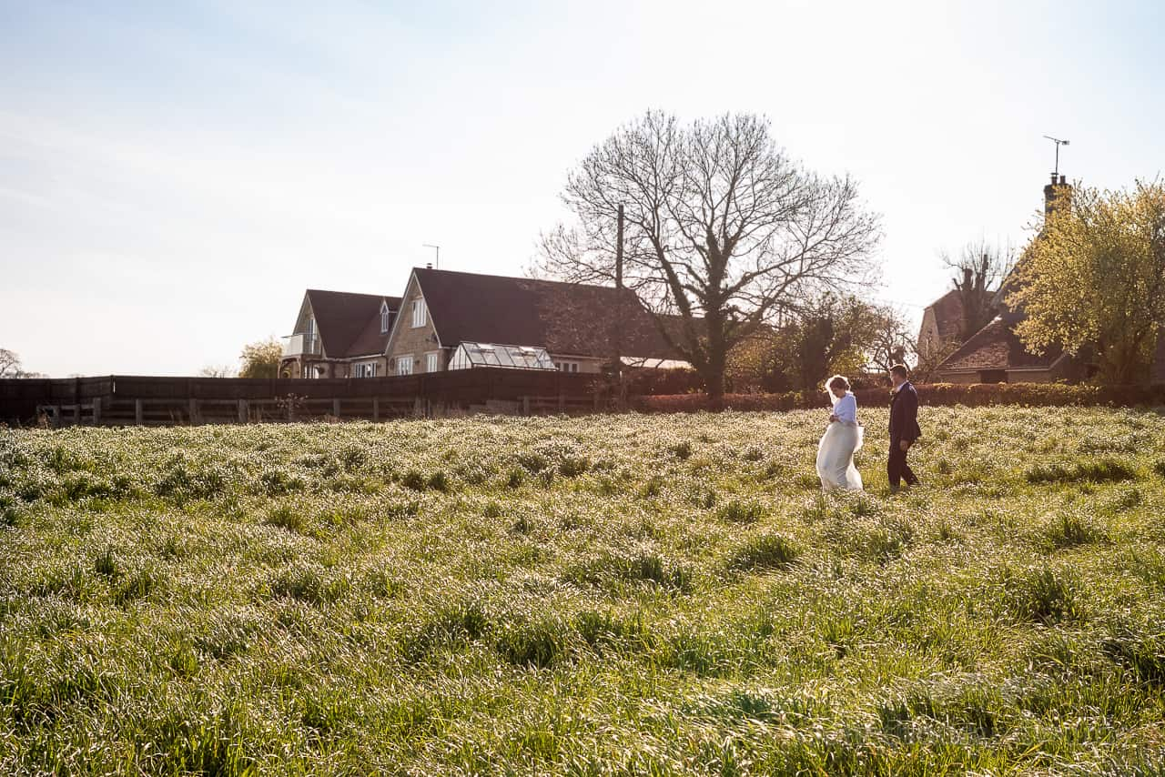 Bride and groom walk through countryside field with nearby houses and low sun