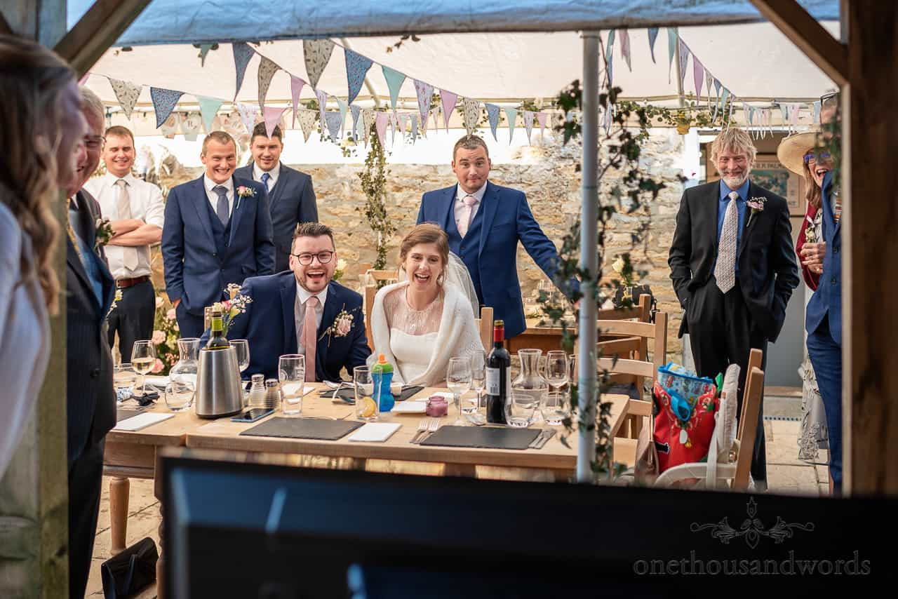 Intimate wedding photography of bride groom and wedding guests laughing reactions to wedding messages video