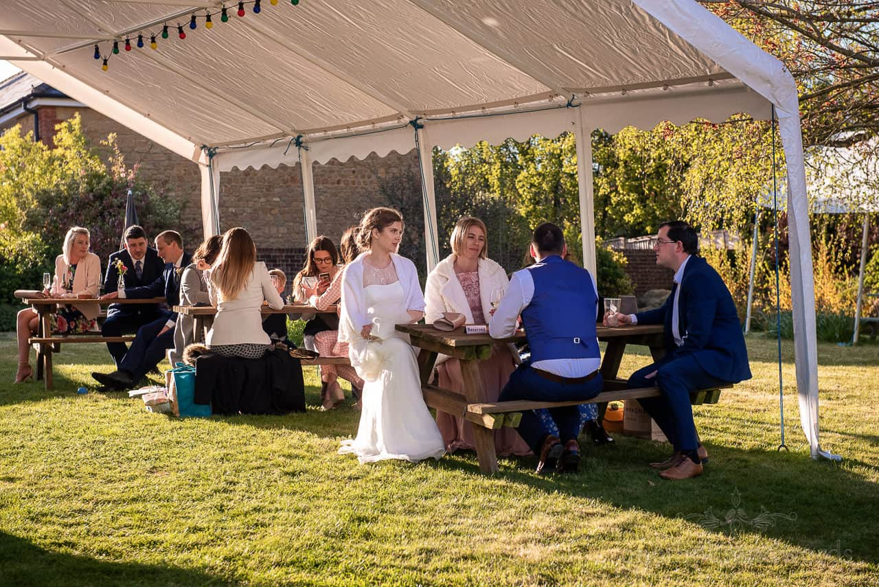 Backlit bride joins wedding party on pub tables under marquee in pub garden
