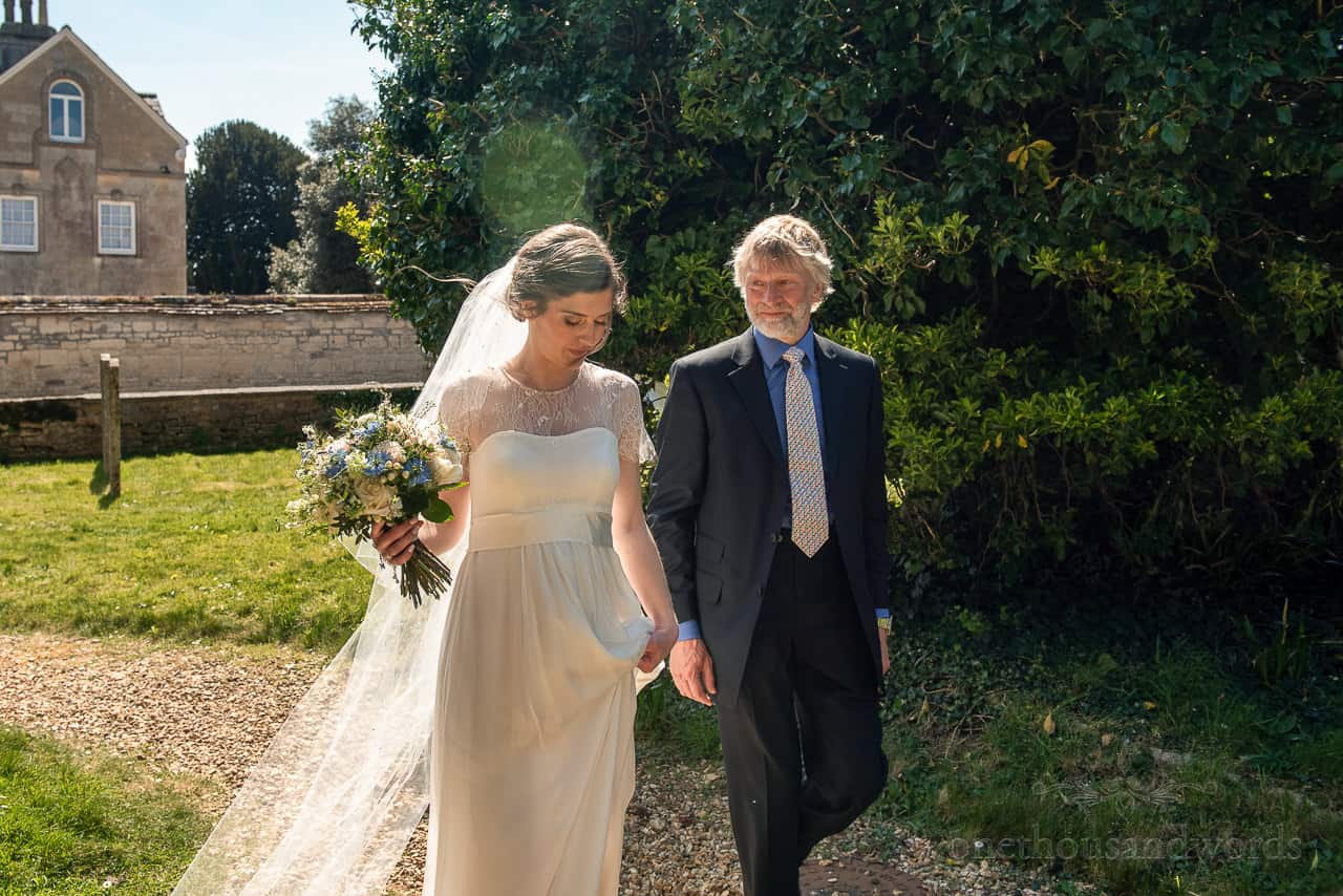 Bride with bouquet and her father walk to church entranceway
