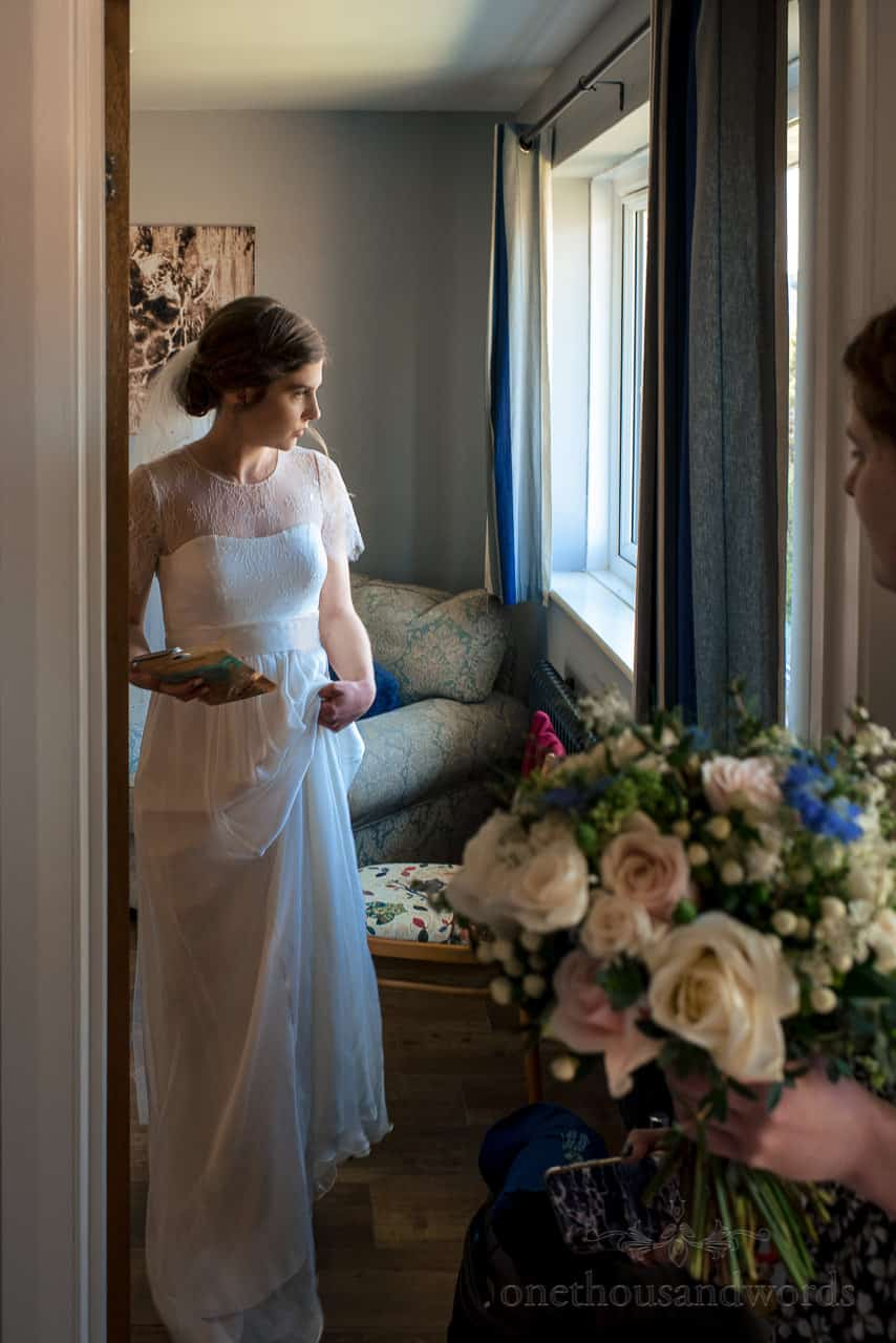 Bride in white wedding dress looks out of window as she leaves for wedding ceremony