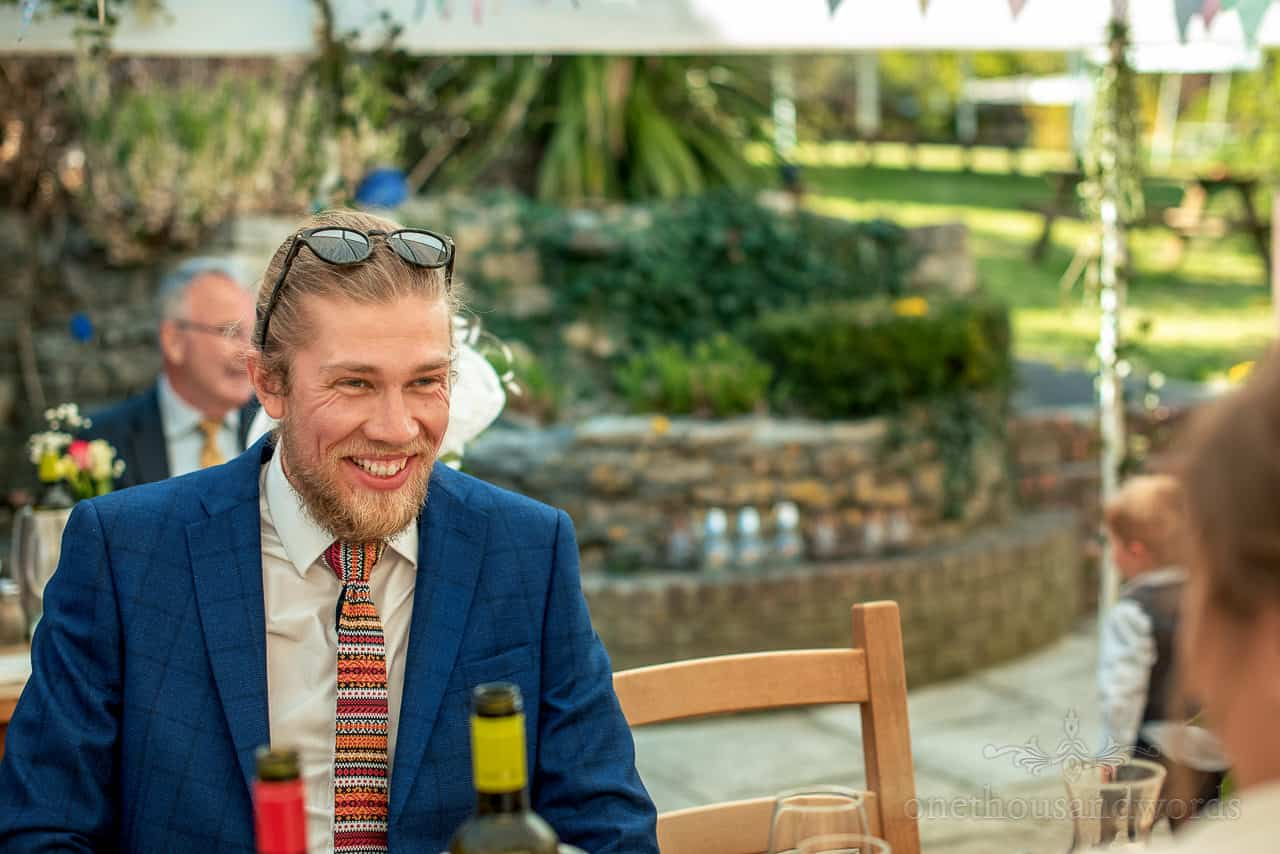 Brides brother in blue suit and funky wedding tie laughing at wedding breakfast