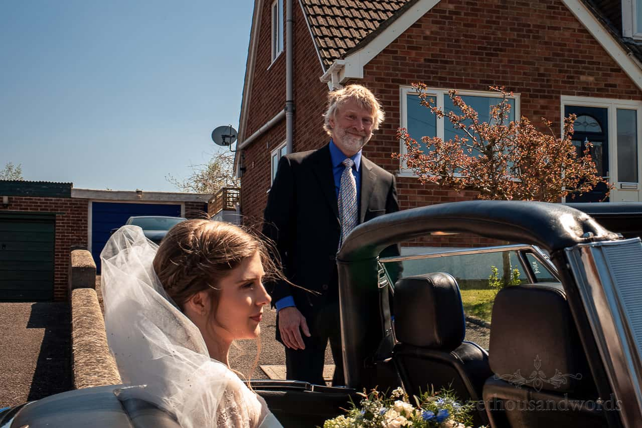 Father watches bride in open top wedding car outside family home