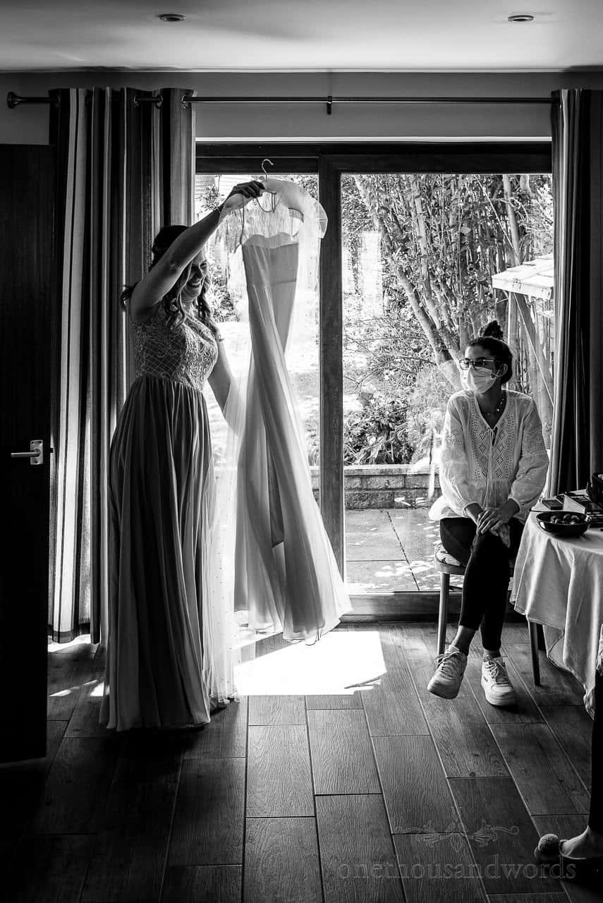 Black and white wedding photo of bridesmaid holding wedding dress on hanger