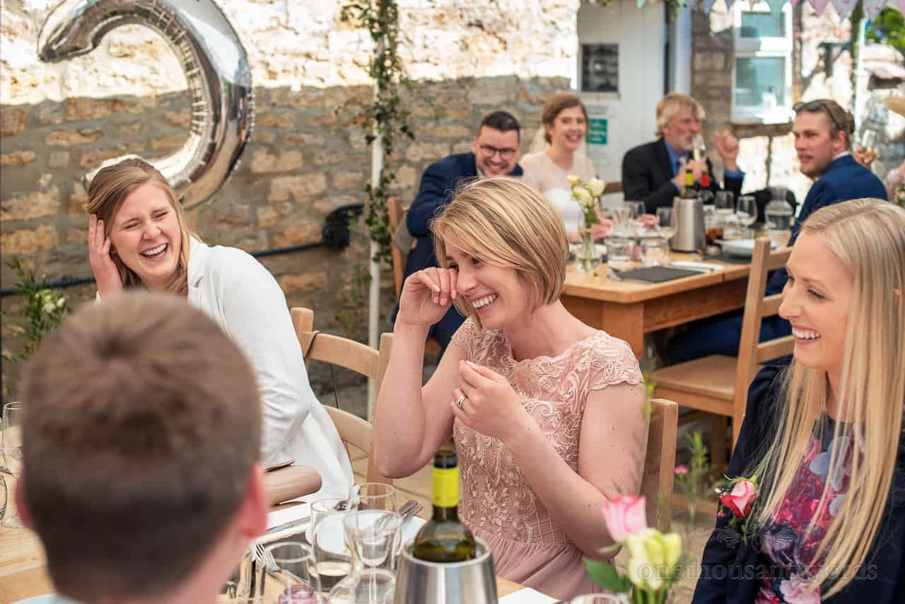 Bridesmaid in pink dress cries with laughter at wedding breakfast
