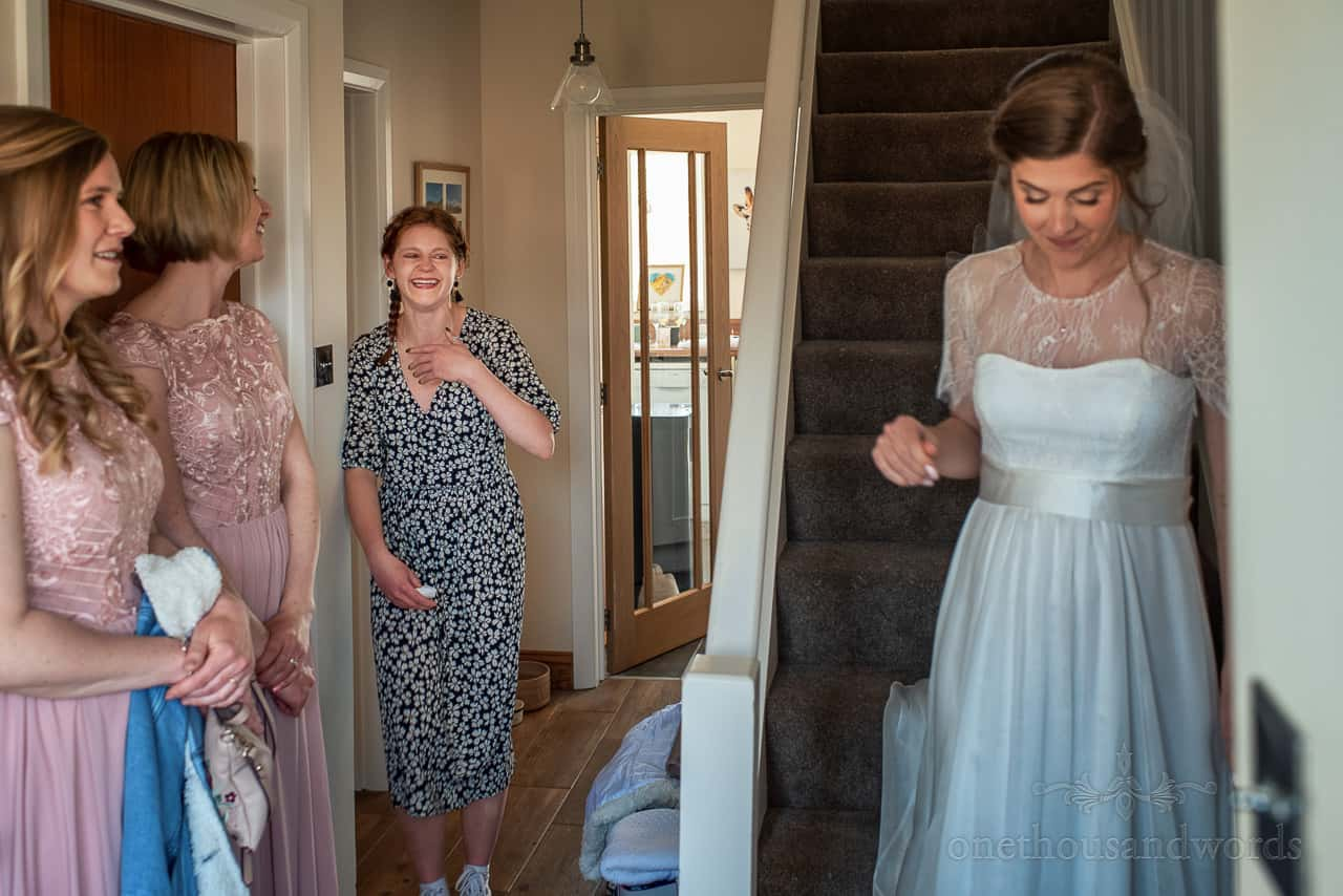 Bridesmaids and friend emotional reaction to seeing bride descend stairs in wedding dress