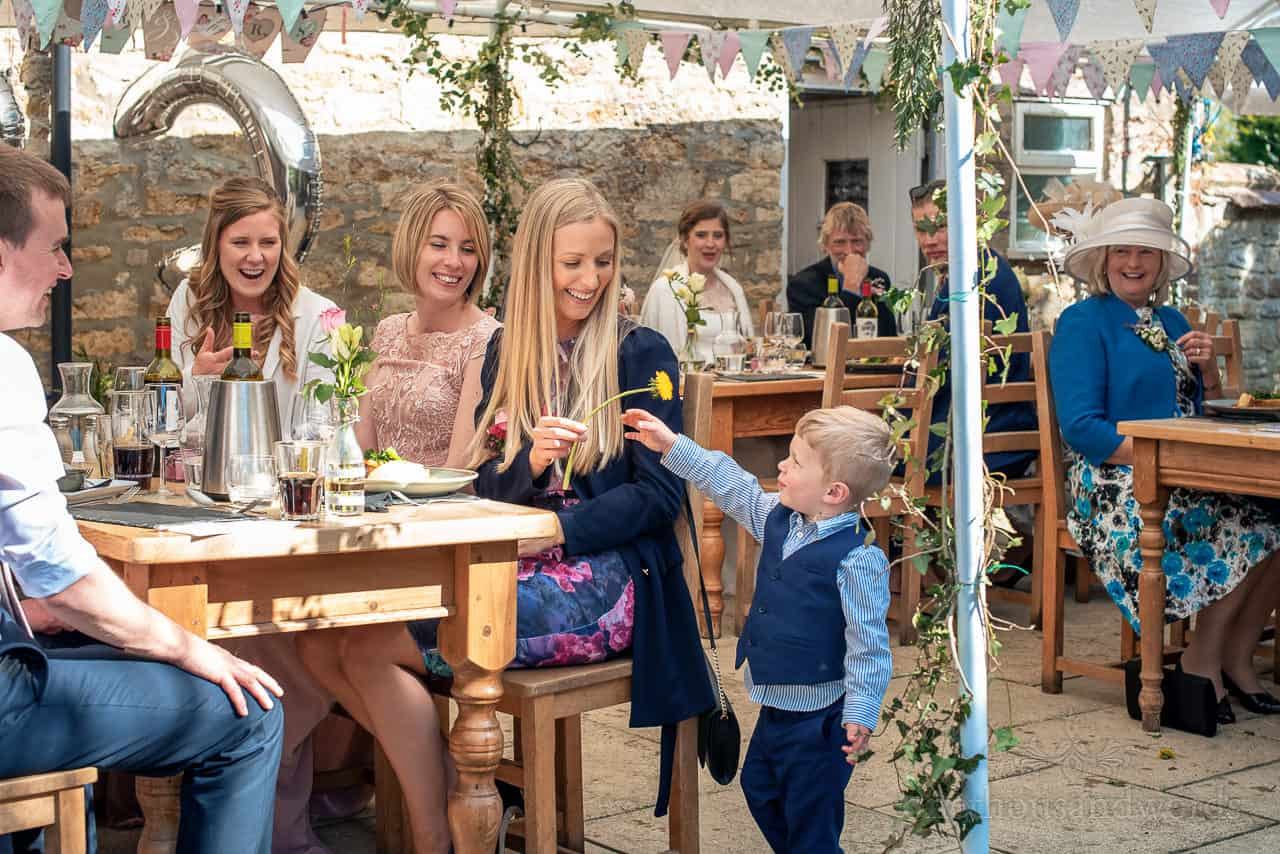 Child wedding guest gives yellow flower to female wedding guests at pub garden intimate wedding breakfast