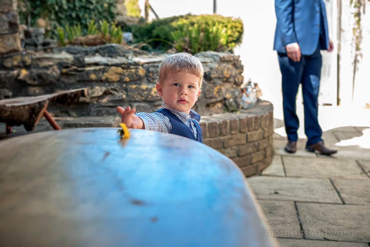 Child wedding guest in blue waistcoat yellow flower on table