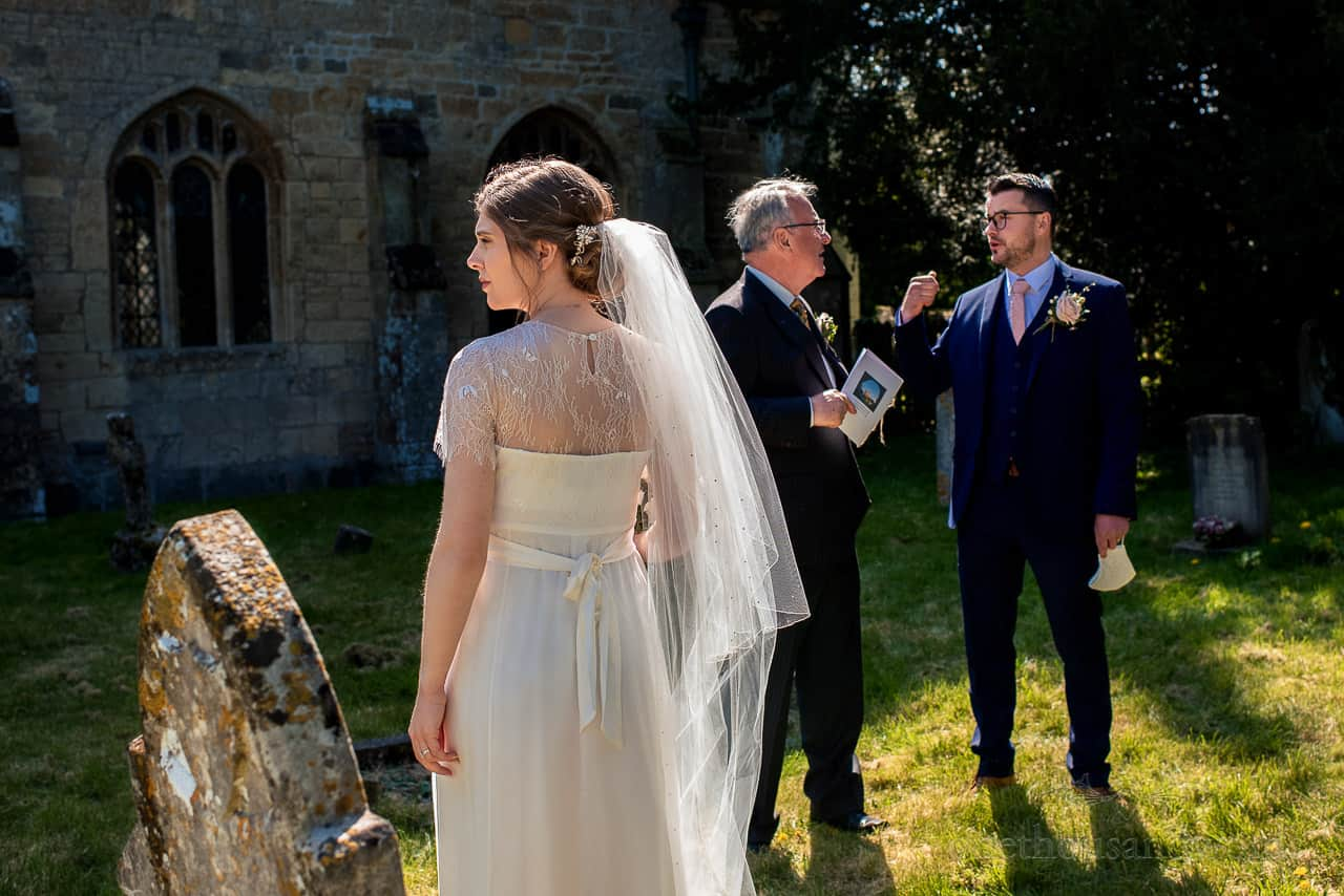 Documentary wedding photograph of bride in bright sunlight outside stone church wedding venue in Dorset
