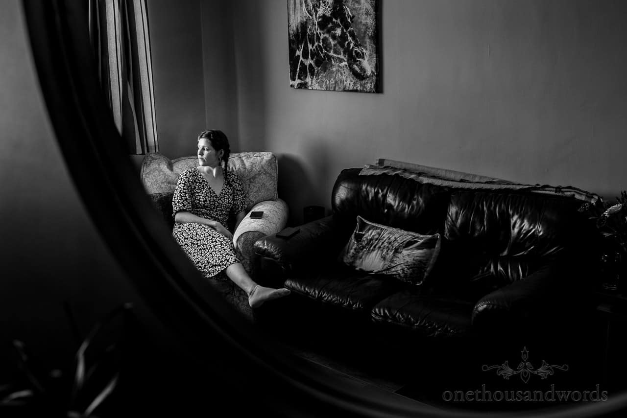 Black and white documentary wedding photo of bridesmaid relaxing on sofa and looking out of window