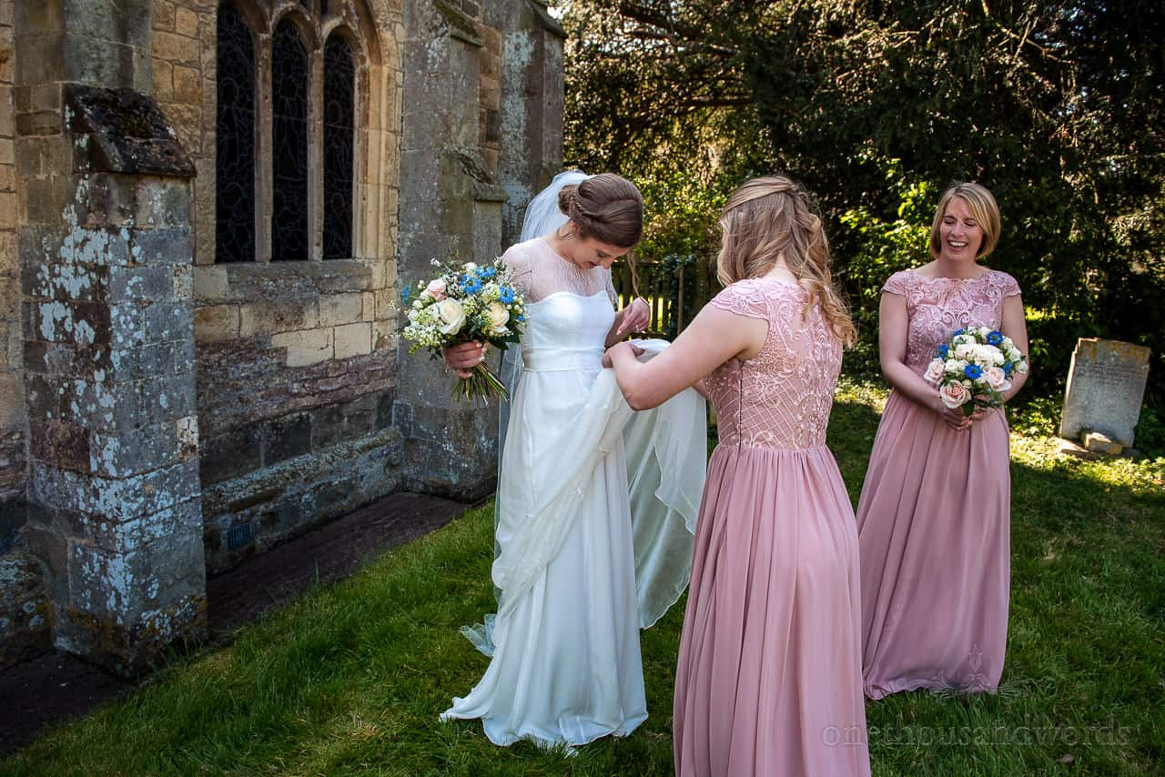 Laughing bridesmaids remove bug from brides wedding dress outside stone church