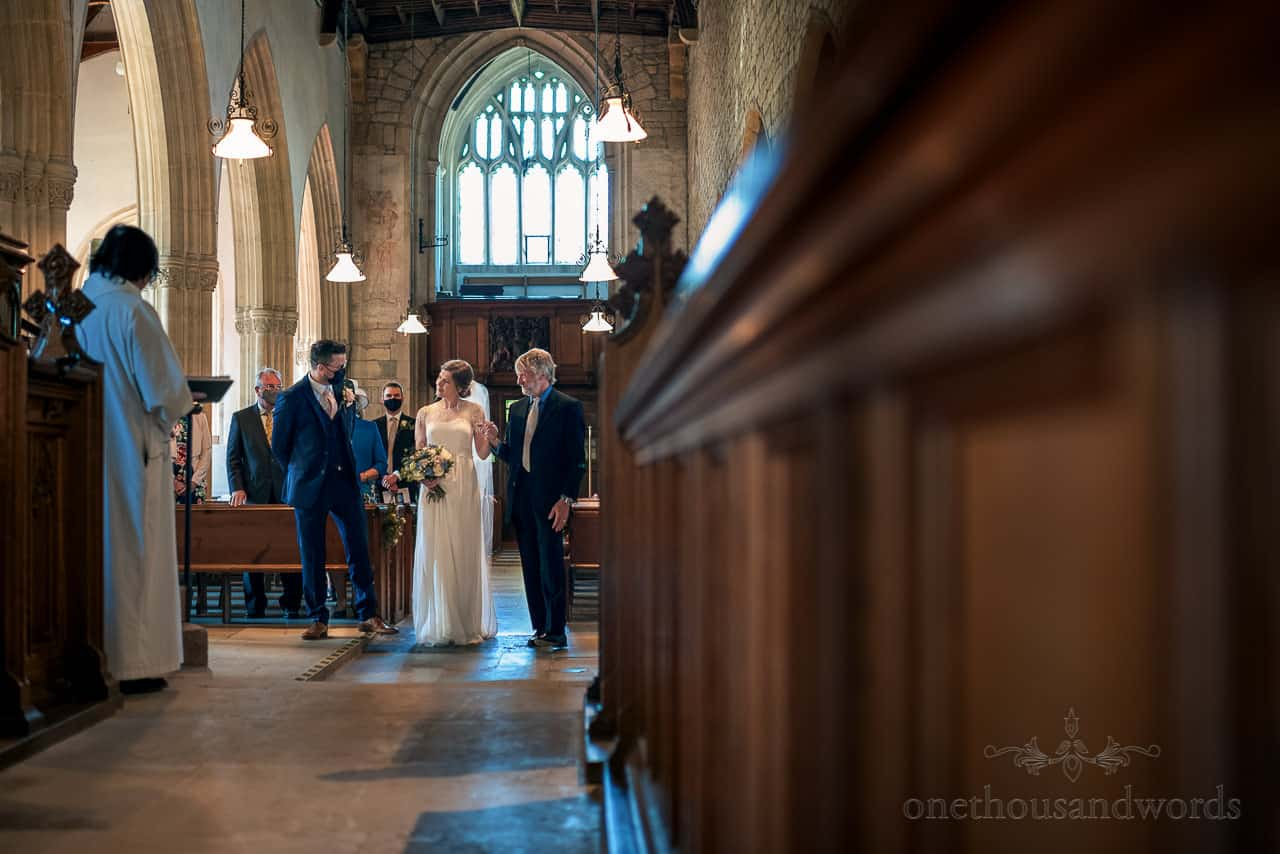 Bride hand in hand with father meets groom at top of church aisle during wedding ceremony from intimate wedding photography
