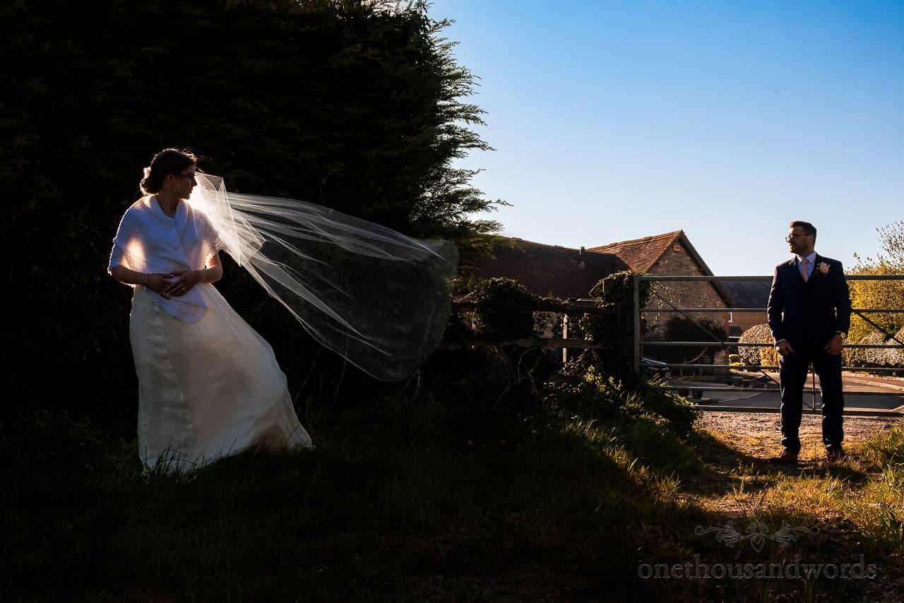 Backlit bride with glowing veil blowing in wind looks at groom in silhouette