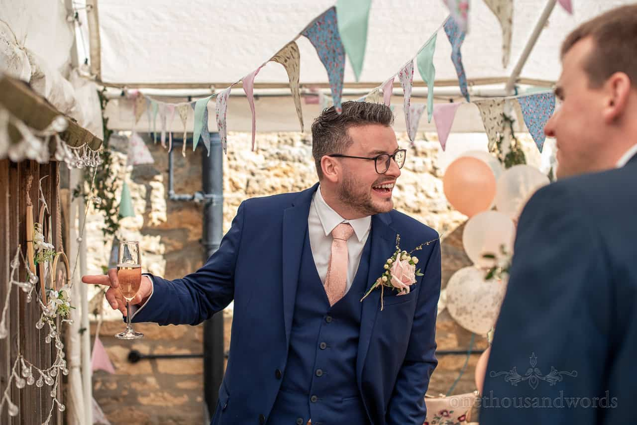 Groom points and laughs at his engagement photos at pub garden drinks reception