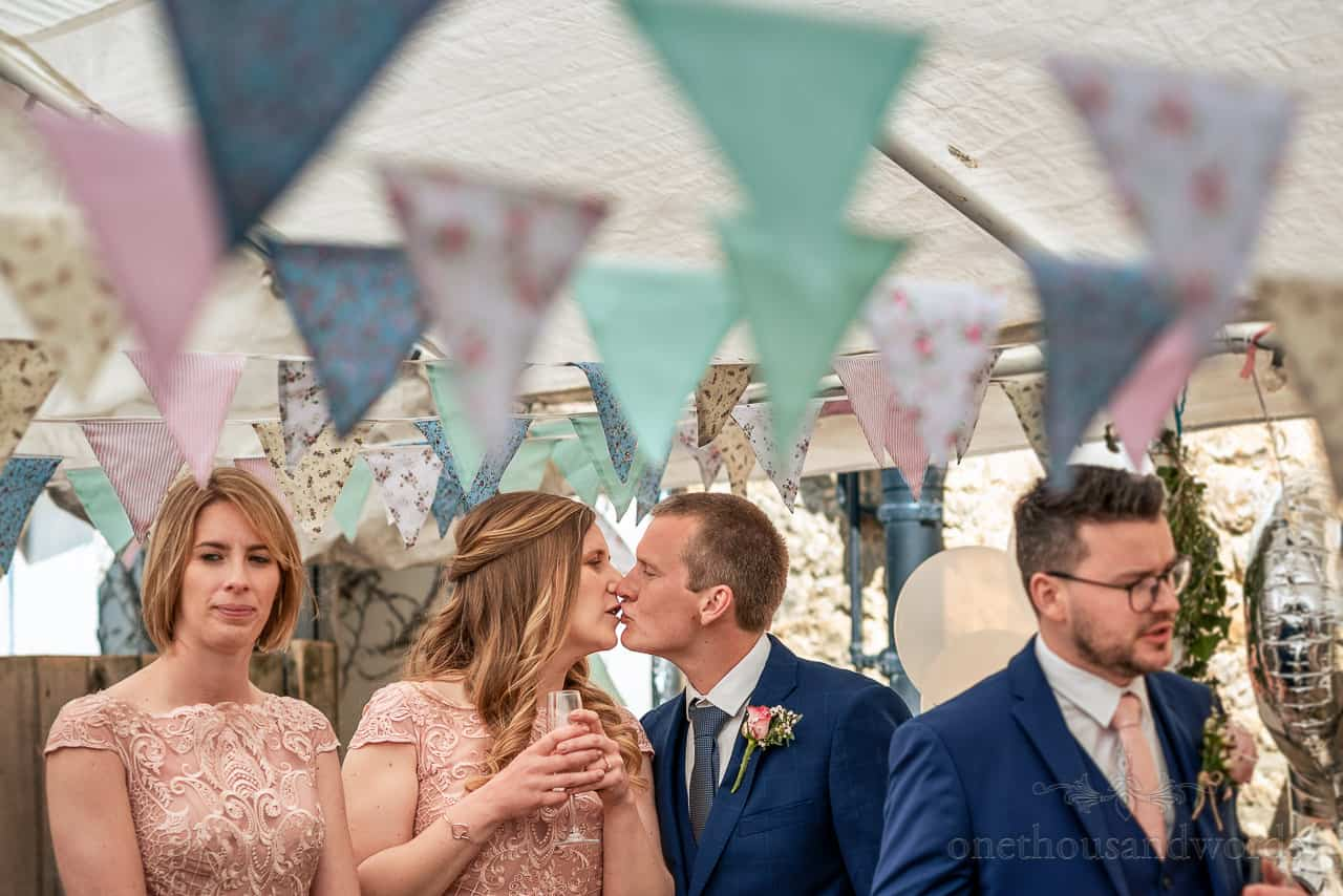 Intimate wedding photography of groomsman in blue suit kisses bridesmaid in pink dress under wedding marquee bunting