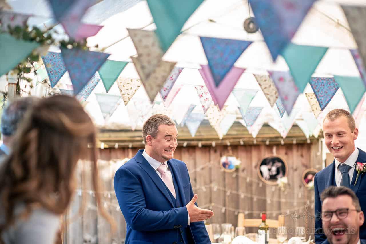 Groomsman in blue suit tells cringing joke under wedding bunting