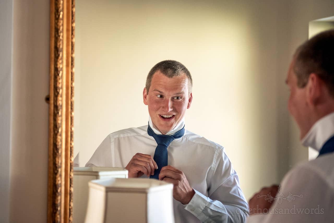 Groomsman looks at his reflection in mirror as he ties blue wedding tie
