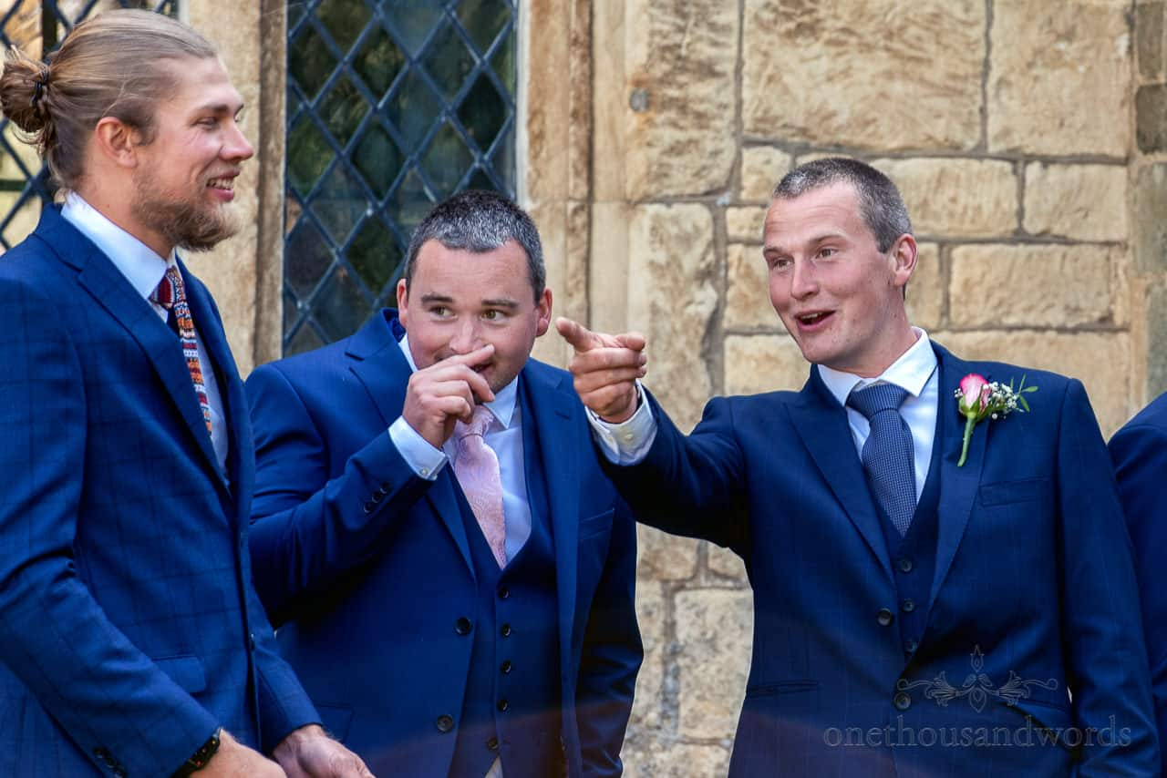Animated groomsmen in blue three pieces suits outside stone church