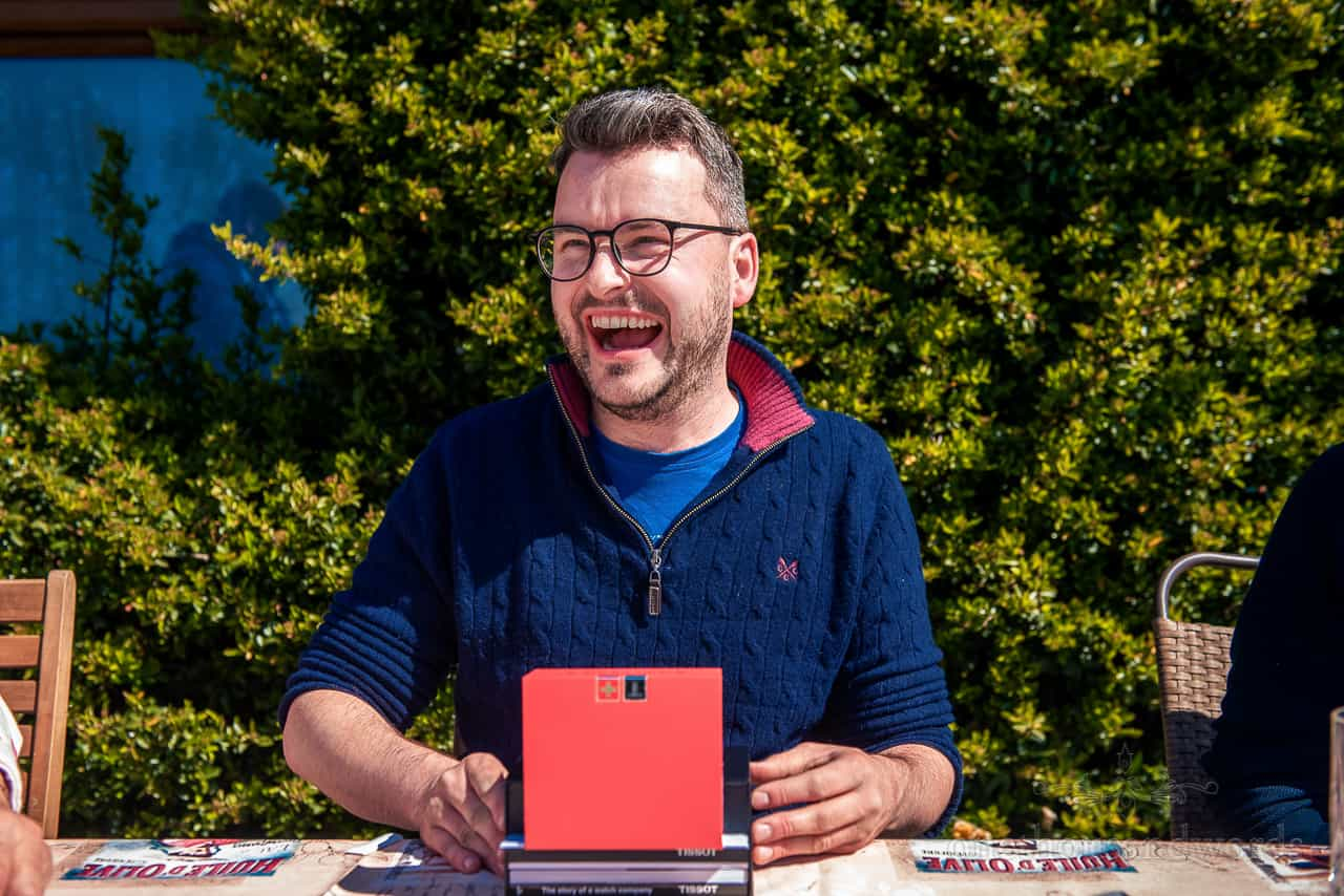Laughing groom in blue jumper receives red watch box wedding morning gift