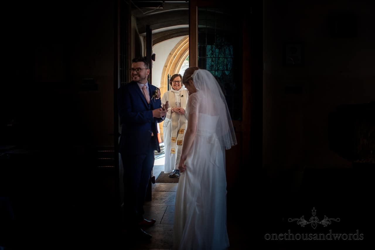 Happy vicar congratulates newlyweds as they prepare to exit church doorway