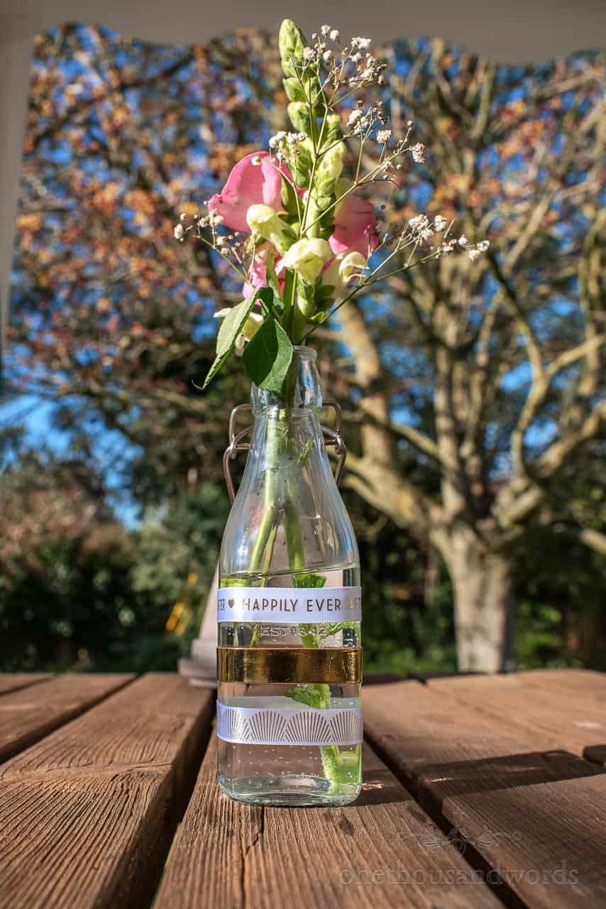Hand made wedding table decoration bottle with flowers and happily ever after ribbon