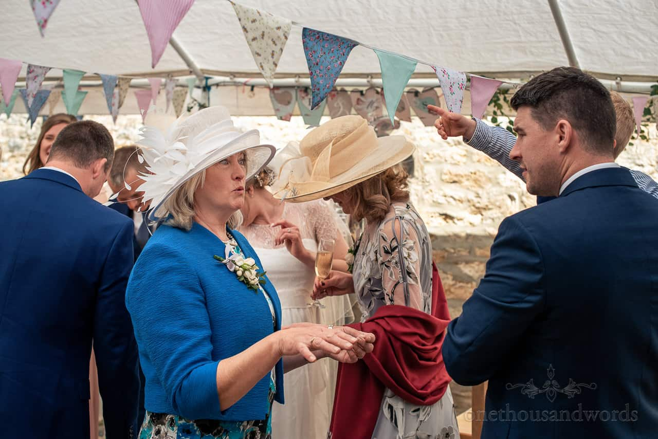 Mother of the bride and groom animated talking to wedding guests in marquee