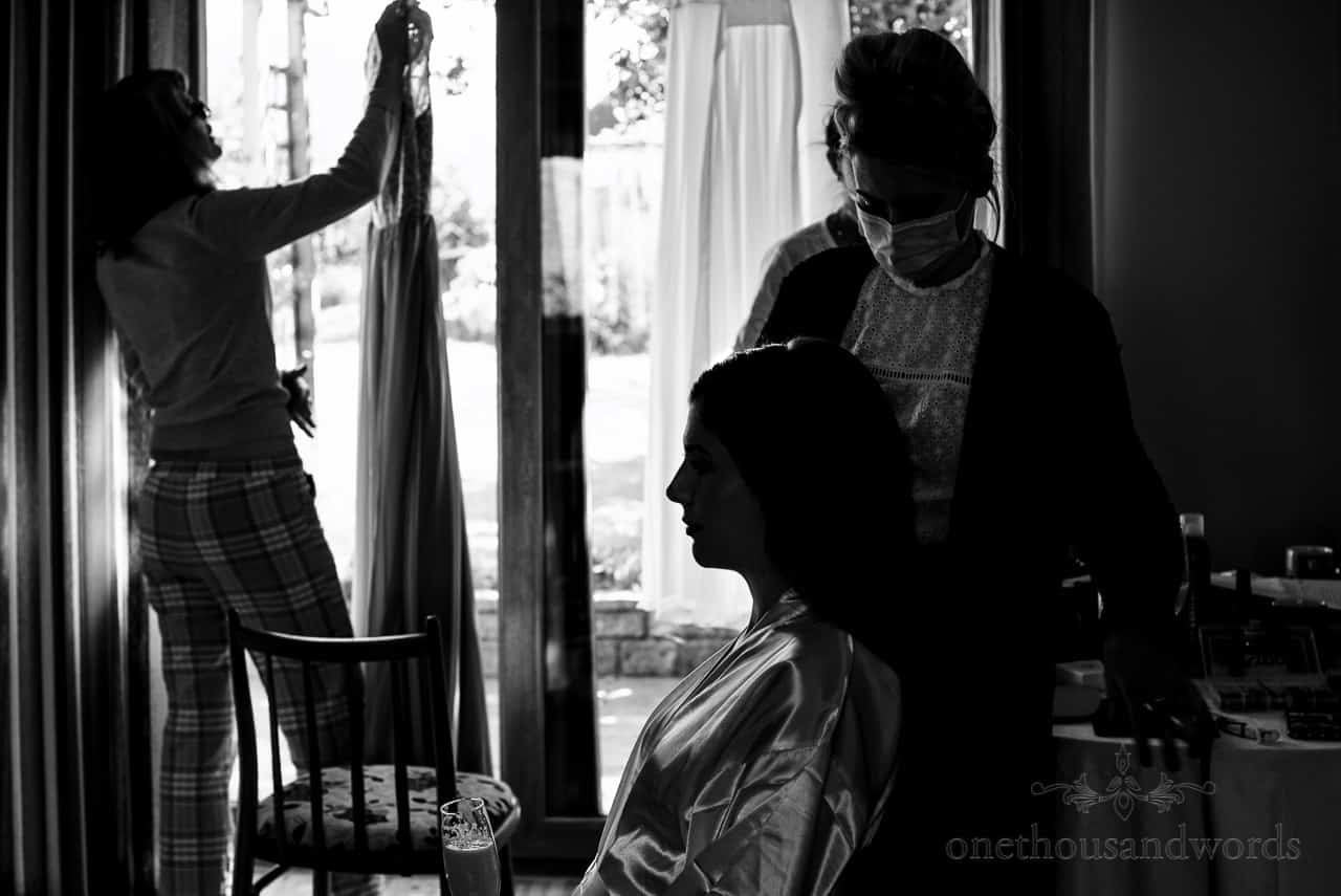 Mother of the bride hangs dress in window as bride has wedding hair styled from intimate wedding photography