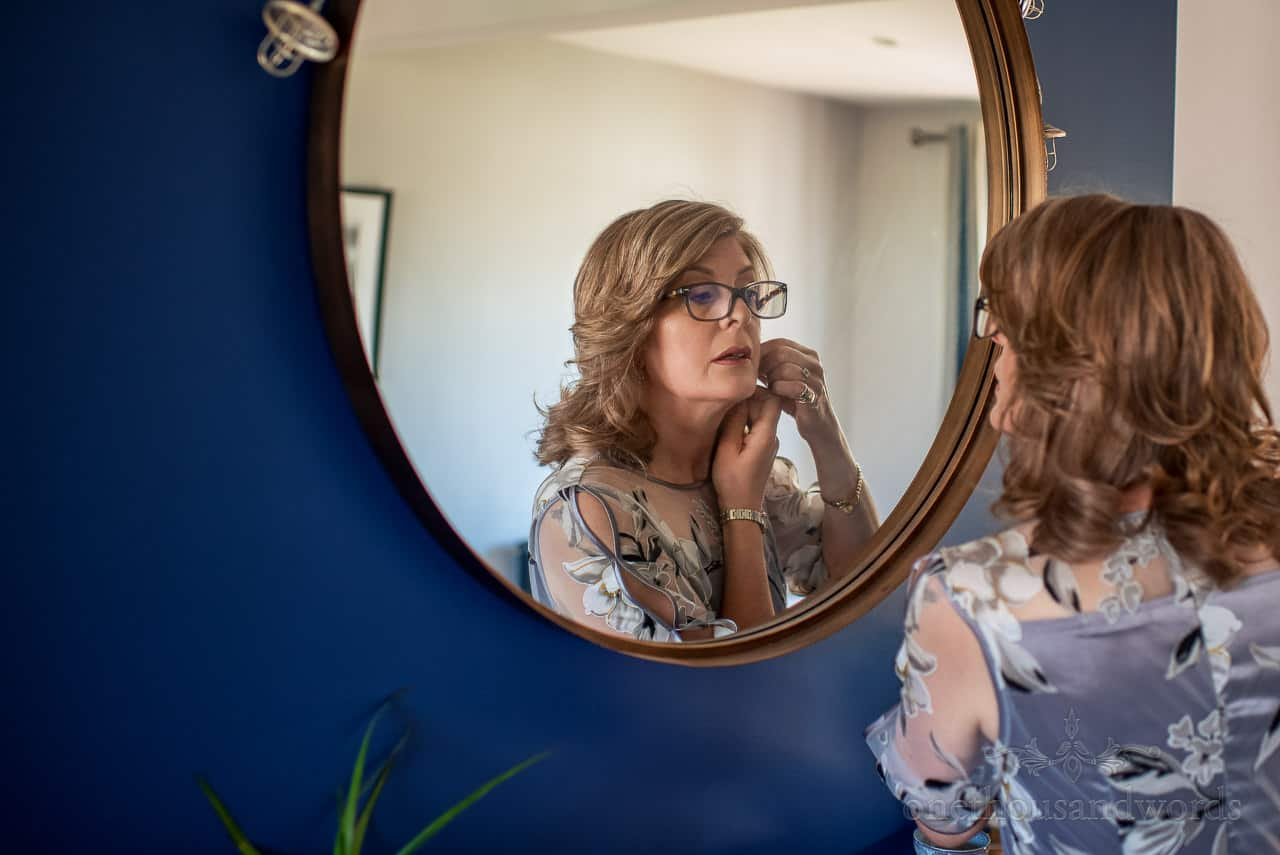 Mother of the bride adjusts earing in circular mirror on blue wall