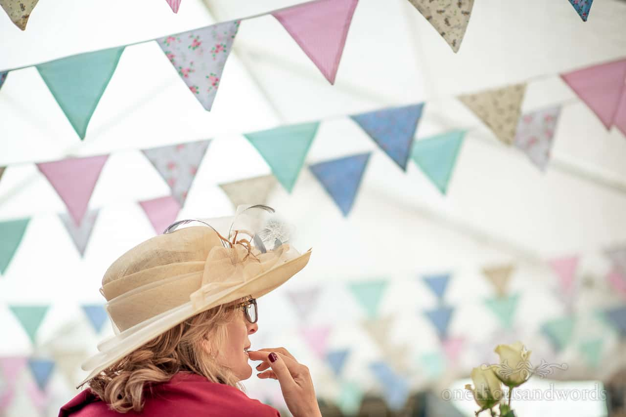 Mother of the bride in red shawl and cream wedding hat under multicoloured wedding bunting