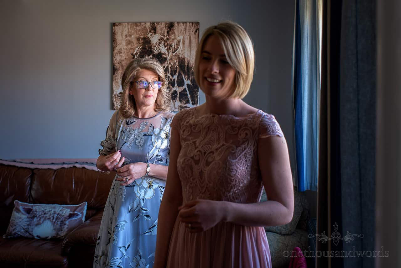 Mother of the bride in silver floral dress and bridesmaid in pink embroidered dress photo
