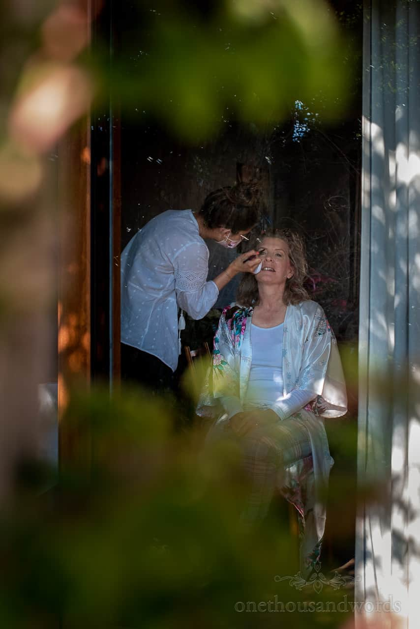Mother of the bride has wedding makeup styled in patio window