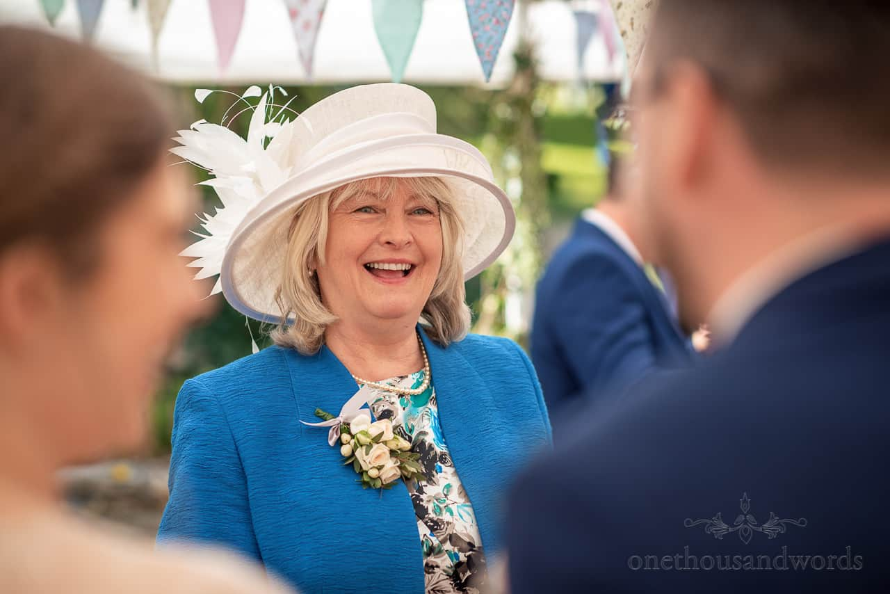 Laughing mother of the groom wears blue jacket and white wedding hat portrait photo