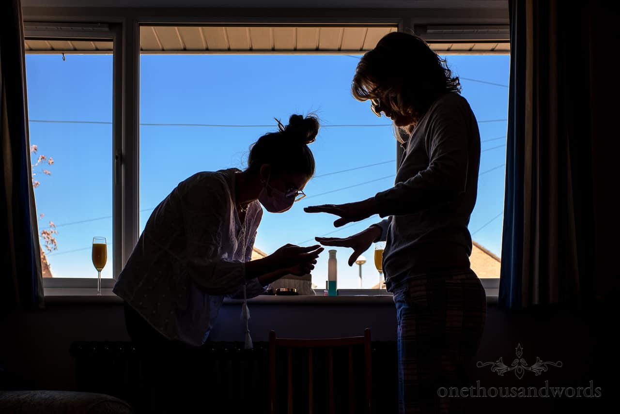 Mother of bride and wedding makeup artist in silhouette against window painting nails