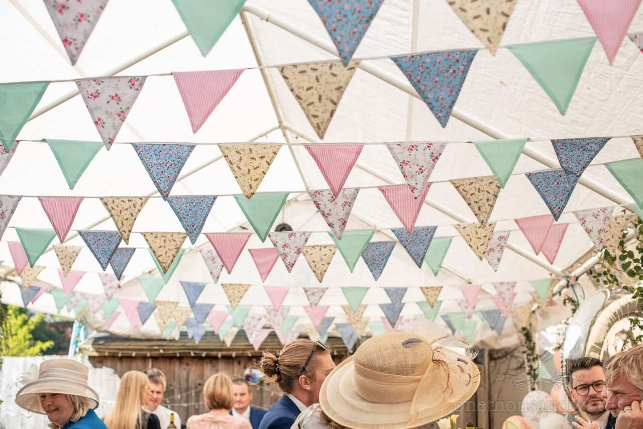 Masses of multi coloured rustic handmade bunting hanging in wedding marquee