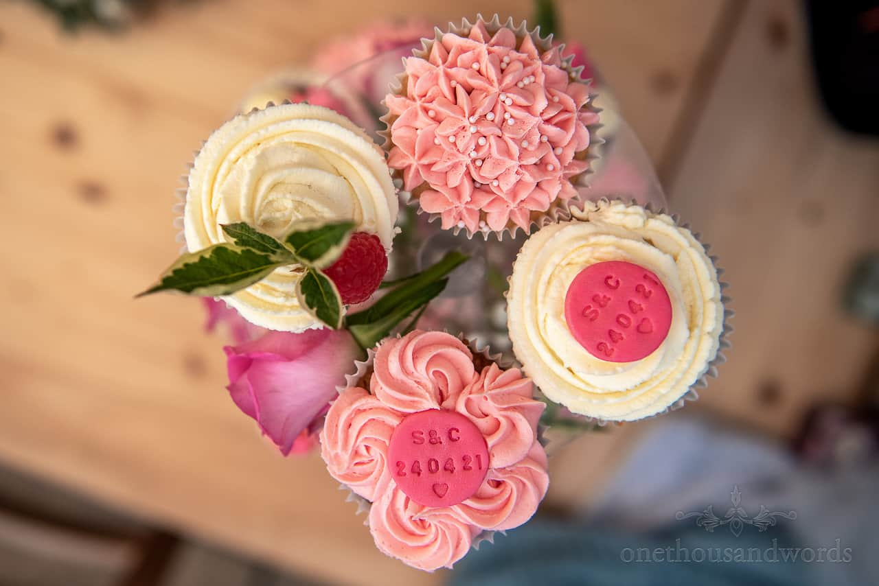 Pink and white patterned icing wedding cupcakes with custom date stamped discs