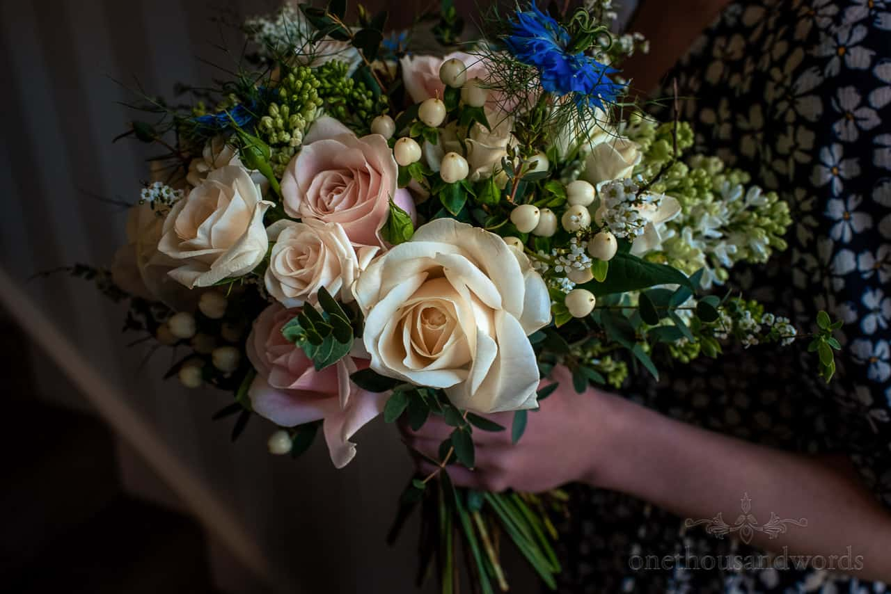 Pink and yellow and blue flowers in green foliage bridal bouquet photo