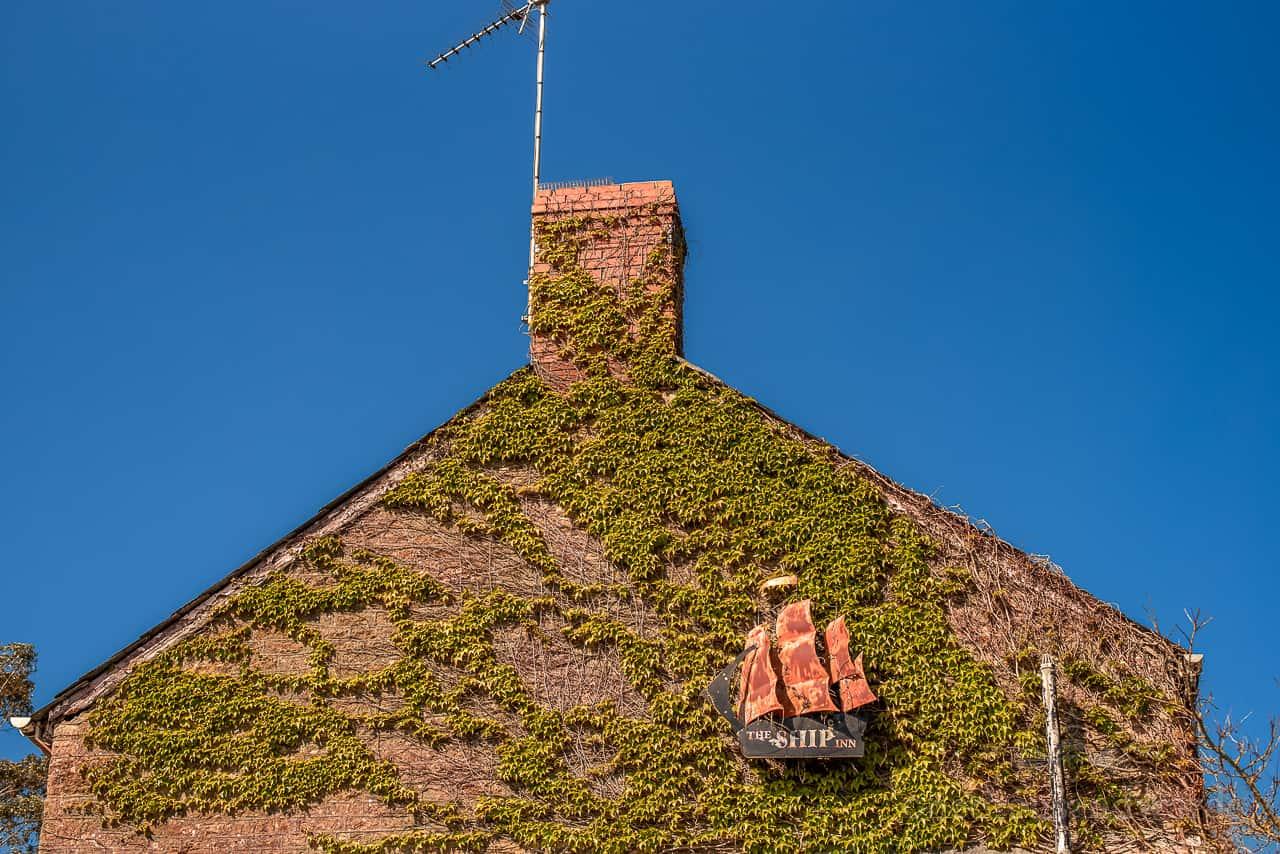 Ship Inn metal pub sign rusting on side of green vine covered pub wall against blue sky